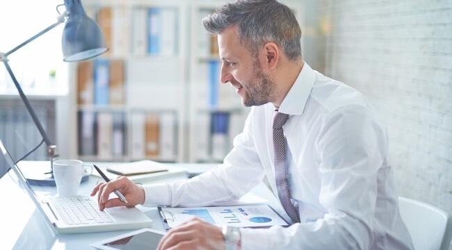 Usmievajúci sa muž v bielej košeli sediaci za stolom v kancelárii. Má pred sebou vytlačené grafy na papieri, v ruke drží pero a píše na notebooku.