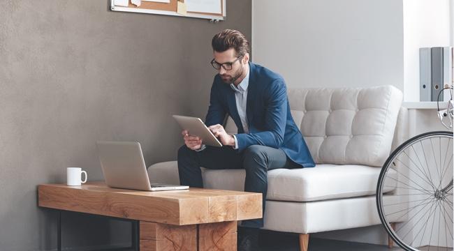 Muž v obleku a okuliaroch sedí na pohovke, v ruke drží tablet, na ktorom si niečo prezerá. Pred ním má na drevenom stolíku položený laptop.