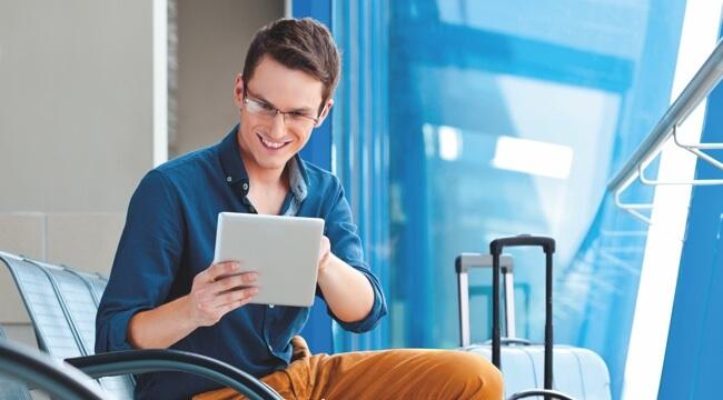 Mladý muž sedí na letisku, v ruke drží tablet, usmieva sa a niečo posiela.