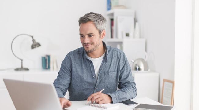 Muž sedí doma za počítačom, pracuje, niečo si zapisuje a usmieva sa.