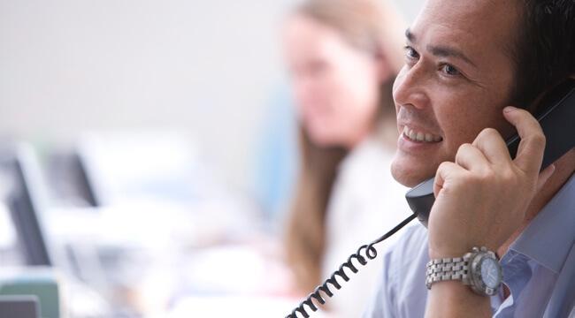 Muž v kancelárii drží telefón pri uchu, telefonuje a usmieva sa.