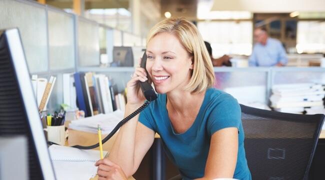 Mladá žena s krátkymi blond vlasmi sedí v kancelárii za stolom. V jednej ruke drží telefón pri uchu a usmieva sa, v druhej ruke drží ceruzku.