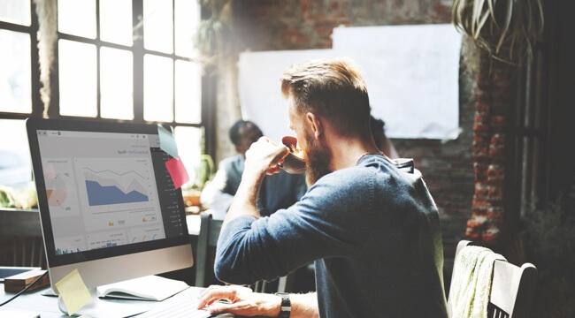 Muž sedí v otvorenej kancelárii, pracuje na počítači. Pravú ruku má na klávesnici, na obrazovke vidíme grafy, v ľavej ruky má šálku, z ktorej pije.